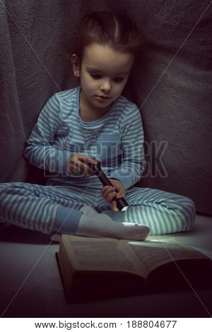 Little girl reading fairy tales book under the covers at the evening with lantern. Cute kid playing before going to sleep, image toned.