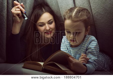 Little girl and her mother reading fairy tales book under the covers at the evening with lantern. Cute kid playing before going to sleep, image toned. Home family leisure.