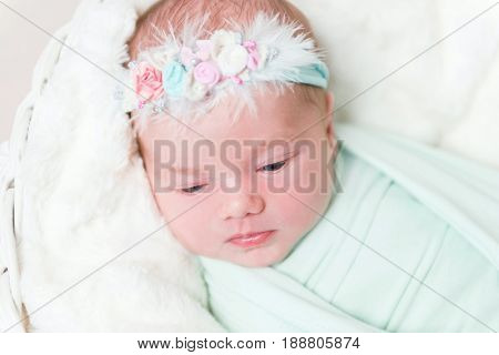 Lovely baby girl with blue flowery headband swaddled in a blue light blanket, awake, closeup