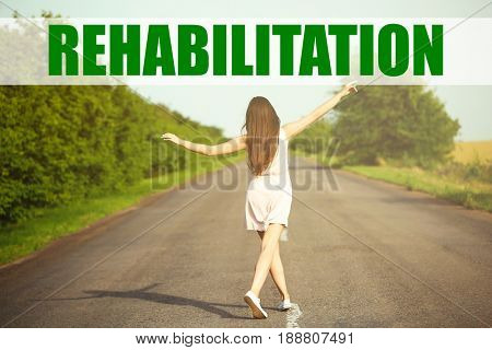 Recovery concept. Woman walking on road. Word REHABILITATION on landscape background