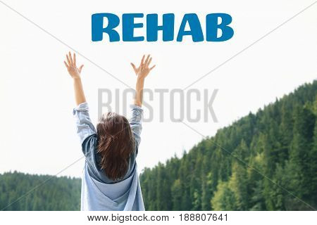 Recovery concept. Word REHAB and woman raising hands on landscape background