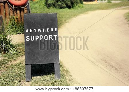 Text ANYWHERE SUPPORT on signboard near countryside road