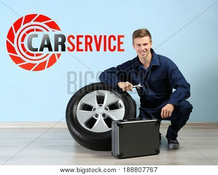 Concept of car service. Mechanic with tool box and wheel on color wall background