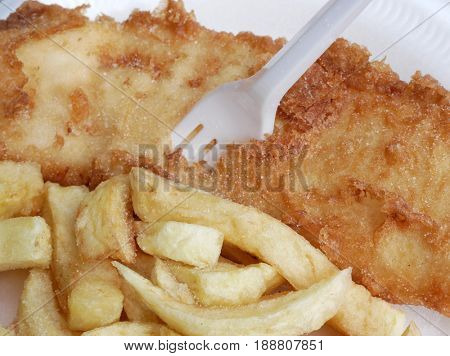 Closeup of traditional, freshly cooked fish and chip meal with plastic fork