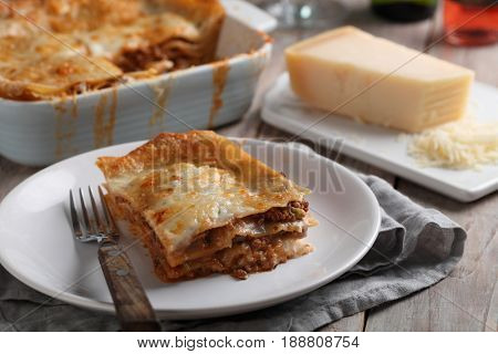 Lasagna Bolognese and Parmesan cheese on a rustic table