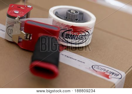 ST. PETERSBURG, RUSSIA - APRIL 28, 2017: Tape gun on the box with lubricants produced by the VMPAUTO enterprise. The company exports products to 35 countries