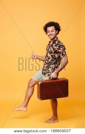 Picture of happy young african man walking over yellow background and holding suitcase. Looking at camera and showing thumbs up.