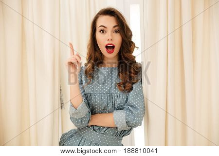 Image of shocked young lady standing in fitting room. Looking at camera have an idea.