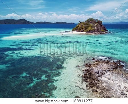 Aerial view of small tropical island with sand bar surrounded by turquoise sea. Palawan May 2017