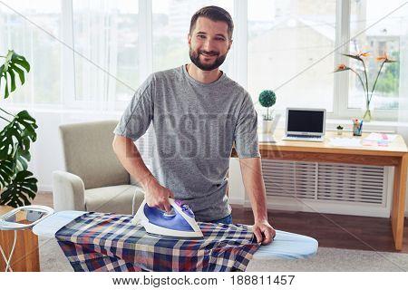 Mid shot of delightful husband ironing diligently shirt on ironing board