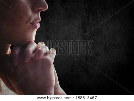 Digital composite of Woman praying against black wall