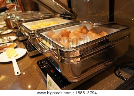 Chafing dish with eggs on table in dining room
