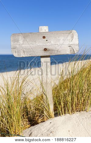 Weathered blank wooden sign between dune grass at the beach