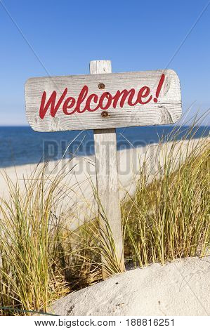 Weathered wooden welcome sign between dune grass at beach