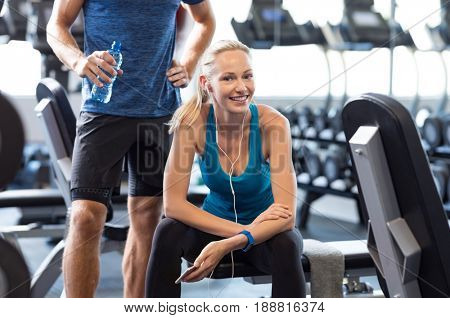 Young woman with smartphone listening to music at gym. Smiling woman at gym relaxing on bench after fitness exercise. Happy girl with phone and earphones take a break from workout.