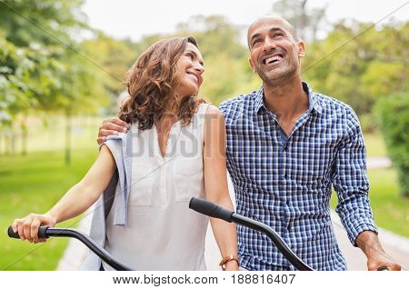 Active mature couple riding bikes during summer vacation. Happy couple cycling and smiling. Cheerful multiethnic couple loving and looking away. Mature woman in love looking her boyfriend.