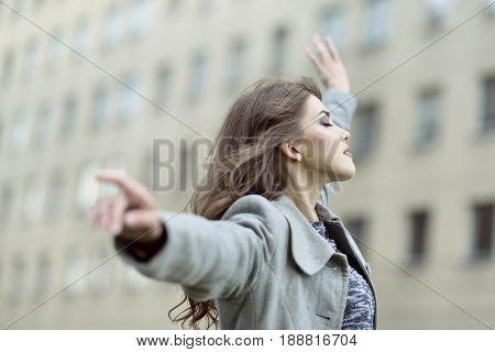 Portrait of girl enjoying live over urban background. Young beautiful woman carefree hovers in the stone jungle of the city. Peace of mind, tranquility, dreaming, placidity and good mood concept