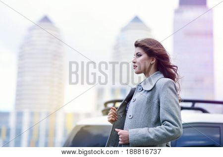 Young pretty girl, spring outdoor portrait. Beautiful woman runing against the backdrop of the urban landscape, image toned.