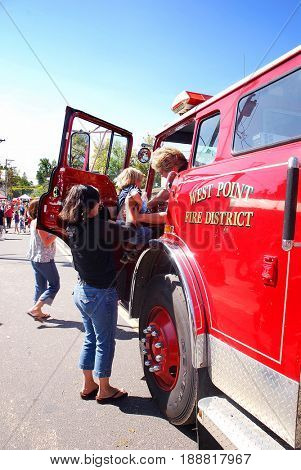 WEST POINT, CALIFORNIA, USA - October 3, 2009: Mother leifts her little boy into a fire truck during the annual Lumberjack Day festival