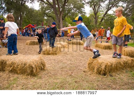 GRANITE BAY, CALIFORNIA, USA - October 18, 2009: Group of Cub Scouts jumping and playing on hay bales at a farm