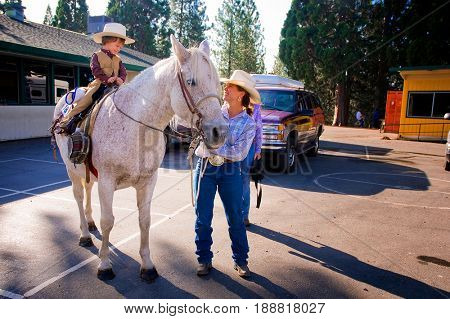 WEST POINT, CALIFORNIA, USA - October 3, 2009: Little cowboy sits on a horse as his mother smiles with him during Lumberjack Day