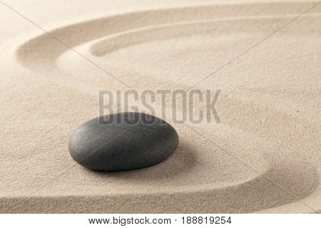 black spa wellness hot stone on raked sand. Zen spiritual and purity texture background.
