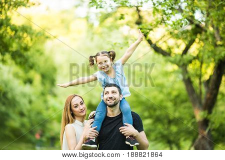 Young Happy Family Of Three Having Fun Together Outdoor. Pretty Little Daughter On Her Father Back.