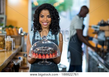 Portrait of smiling waitress holding a cake stand with chocolate cake in cafe