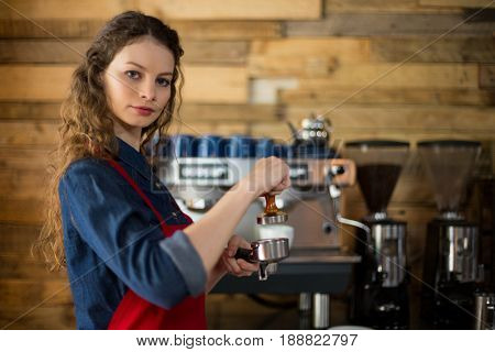 Waitress using a tamper to press ground coffee into a portafilter in cafe