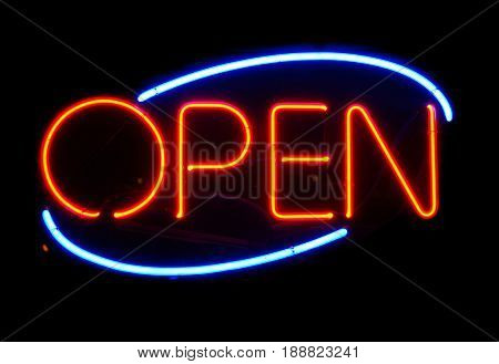 Open neon sign hanging in a window