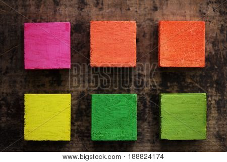 Index, menu or cover abstract back ground, consisting of six hand painted colored wooden cubes on grungy wooden background. fluorescent colors.yellow, orange, pink, green.