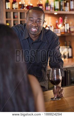 African American bartender serving customer