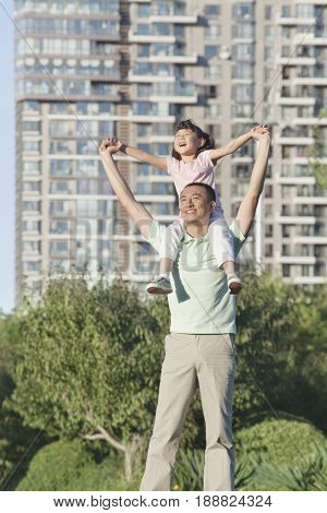 Chinese father carrying daughter on shoulders