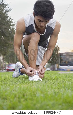 Chinese man kneeling and tying shoes