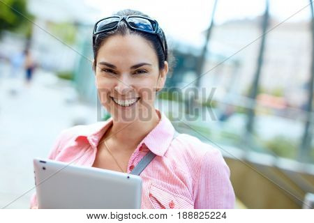 Happy young adult woman outdoor on the street laughing. Lifestyle portrait photo with copyspace.