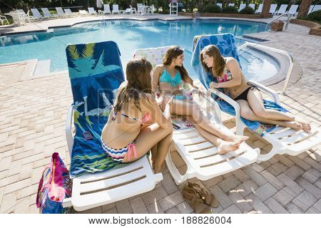 Caucasian teenagers sunbathing at poolside