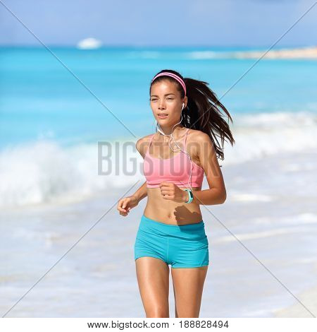Woman runner wearing fitness activity tracker smartwatch listening to music with headphones and phone app. Asian girl athlete training on morning run on beach.