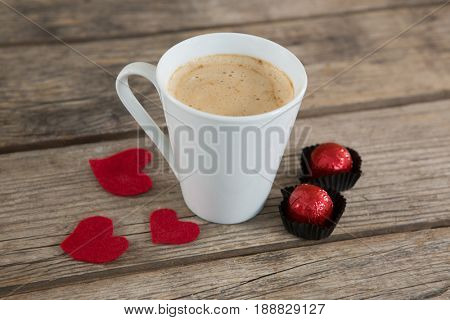 Cup of coffee with chocolates and red heart shape rose petals on wooden surface