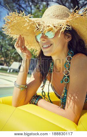woman in bikini sunbathing on air mattress in the swimming pool