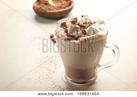 Cup of tasty cocoa drink with marshmallow on light background