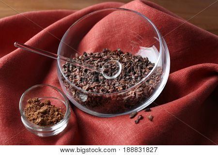 Bowls with cocoa nibs and powder on color cloth