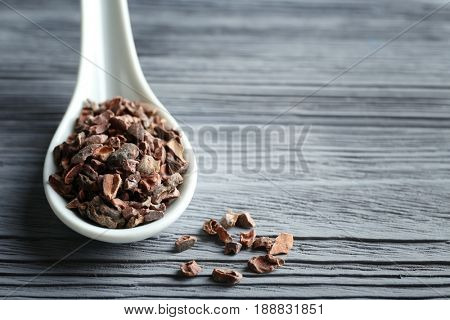 White spoon with cocoa nibs on wooden table