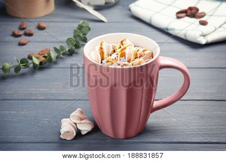 Cup of tasty cocoa drink with marshmallow on wooden table