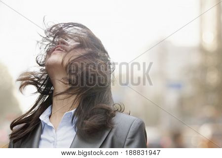 Wind blowing Chinese businesswoman's hair