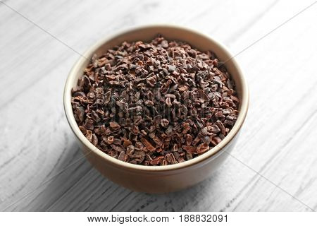 Bowl with cocoa nibs on wooden background