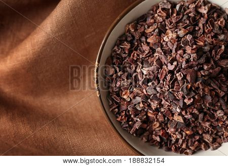 Bowl with cocoa nibs on brown cloth background