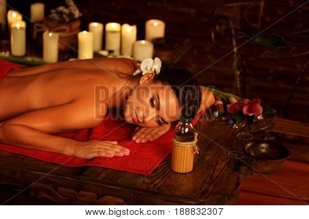 Massage of woman in spa salon. Girl on candles background in massage and skincare spa salon. Luxary interior with white orchid in oriental therapy salon. Female bare back with smooth skin have relax .