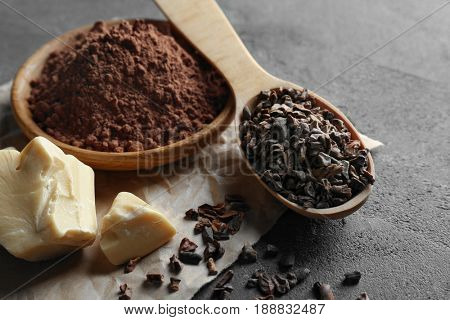 Composition with cocoa nibs, butter and powder on gray background