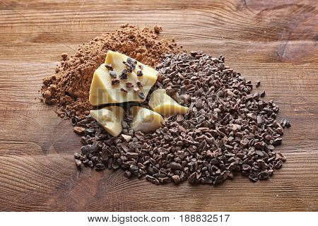 Cocoa nibs, butter and powder on wooden background