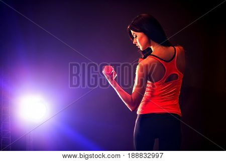 Fitness girl exercising in gym with dumbbells. Woman has slim stomach works in multi-colored rays of sport room. Portrait of full-length in profile. Back view of beautiful back.